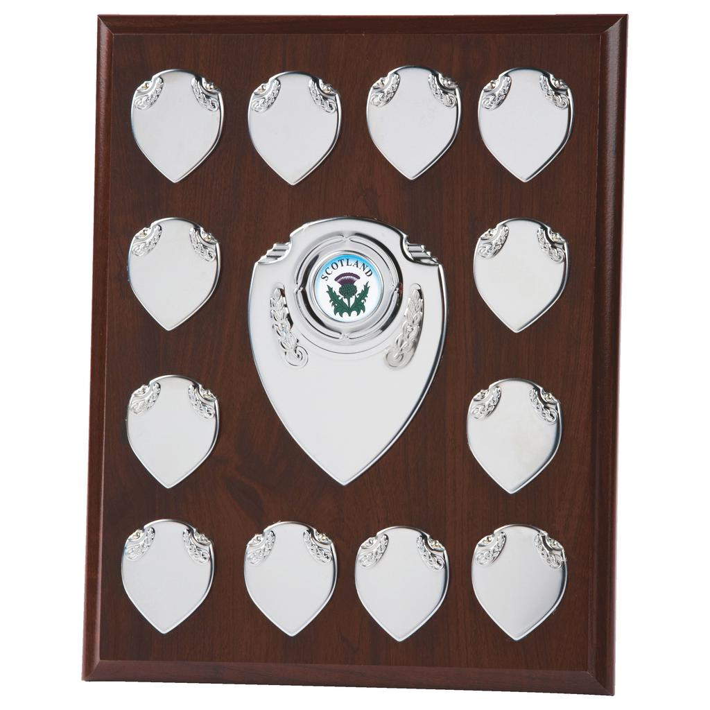 Annual Presentation Plaque 25.5cms made from a MDF based material with a dark colour finish and a sturdy strut on the rear. Incorporating ten small record shields, and chrome coloured centre embellishments.