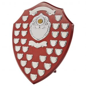 Annual Presentation Shield 46cms made from a MDF based material with a hard wearing rosewood colour finish and a sturdy strut on the rear. Incorporating twenty small record shields, two scrolls and chrome coloured centre embellishments
