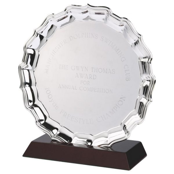 Nickel Plated Salver and Base 25cm. Made from a metal alloy with a bright shiny finish and rosewood slotted base. Incorporating large area to include any engraving if required. If required engraving is available for a small charge. Option to add a logo