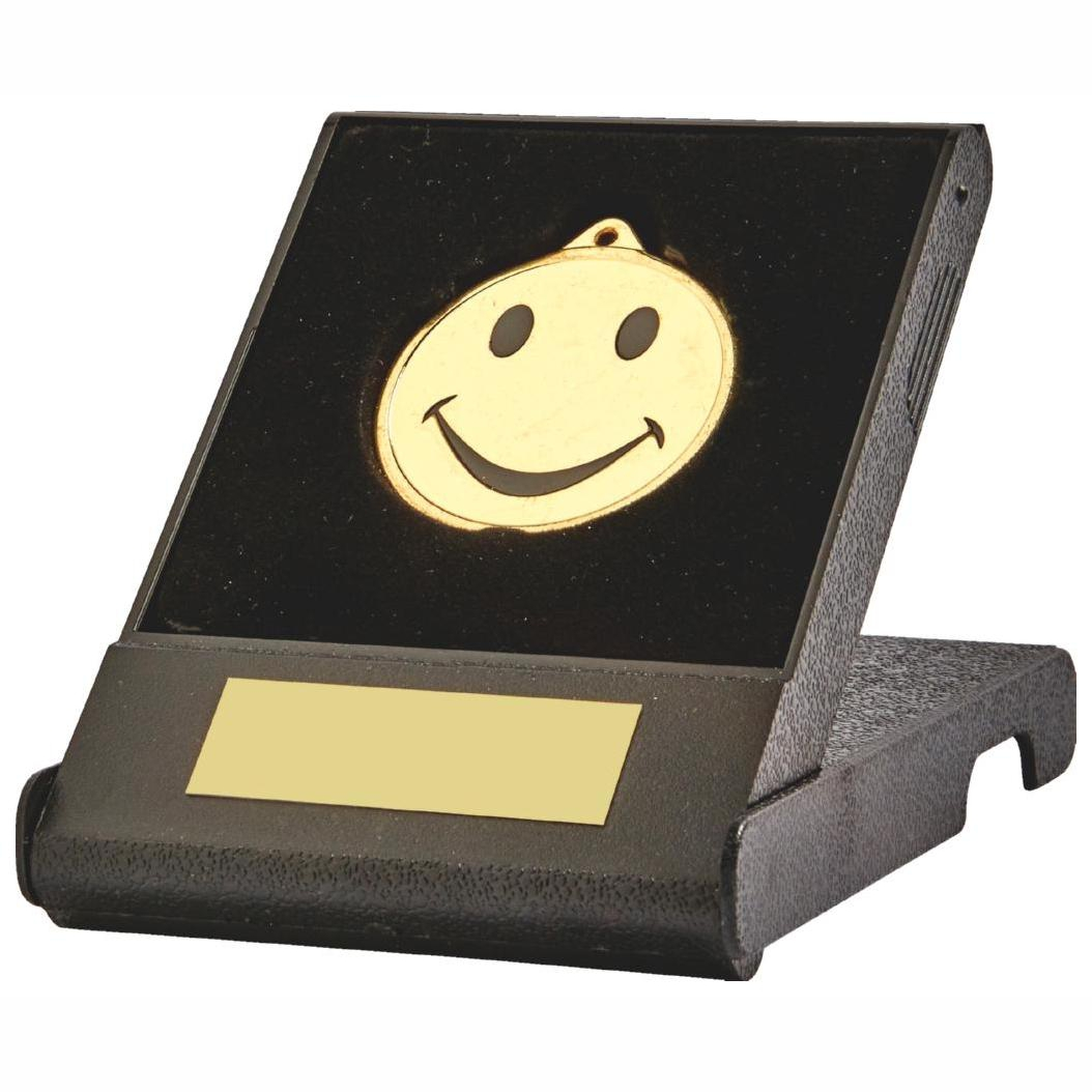 Black coloured moulded plastic open and shut flip box with a standard 45mm dia printed happy face medal sits in a black coloured recessed liner