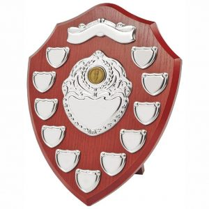 annual-presentation-shield-30cms is made from a MDF based material with a hard wearing rosewood colour finish and a sturdy strut on the rear. Incorporating eleven small record shields and chrome coloured centre and scroll embellishments.