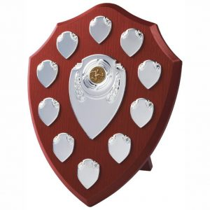 Annual Perpetual Shield 30cms tall made from a MDF based material with a hard wearing rosewood colour finish and a sturdy strut on the rear. Incorporating seven small record shields, and chrome coloured centre embellishments.