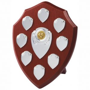 Annual Perpetual Shield 25cms tall made from a MDF based material with a hard wearing rosewood colour finish and a sturdy strut on the rear. Incorporating seven small record shields, and chrome coloured centre embellishments.