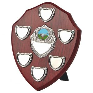 Clearance Line Annual Presentation Shield 20cms Made from a MDF based material with a hard wearing rosewood colour finish and a sturdy strut on the rear. Incorporating nine small record shields, scroll and chrome coloured centre embellishments